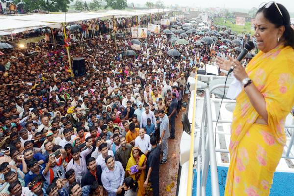 तेज बारिश हो रही थी, फिर भी छाते लेकर मुख्यमंत्री राजे को सुनने उमड़े लोग